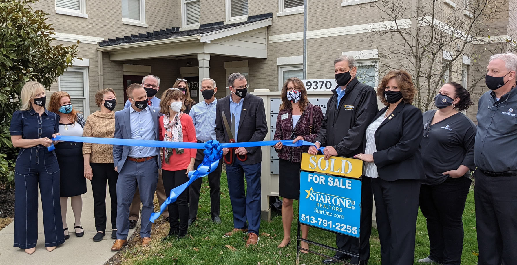 """Thirteen people standing in front of a building, while three hold a blue ribbon and a """"Sold"""" sign is in front"""