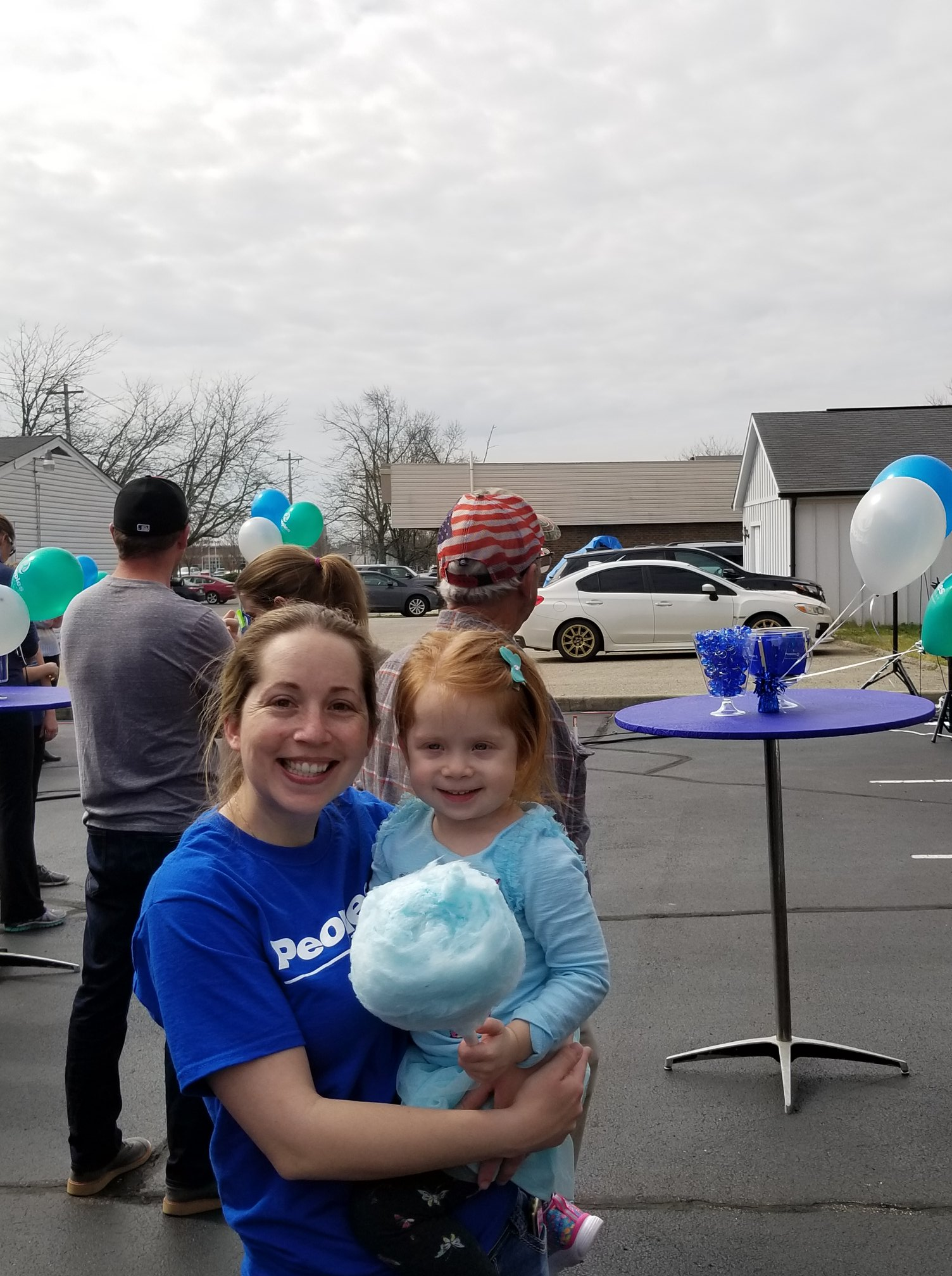 Two girls smiling for the camera and a man is standing facing backwards in the background with balloons scattered around
