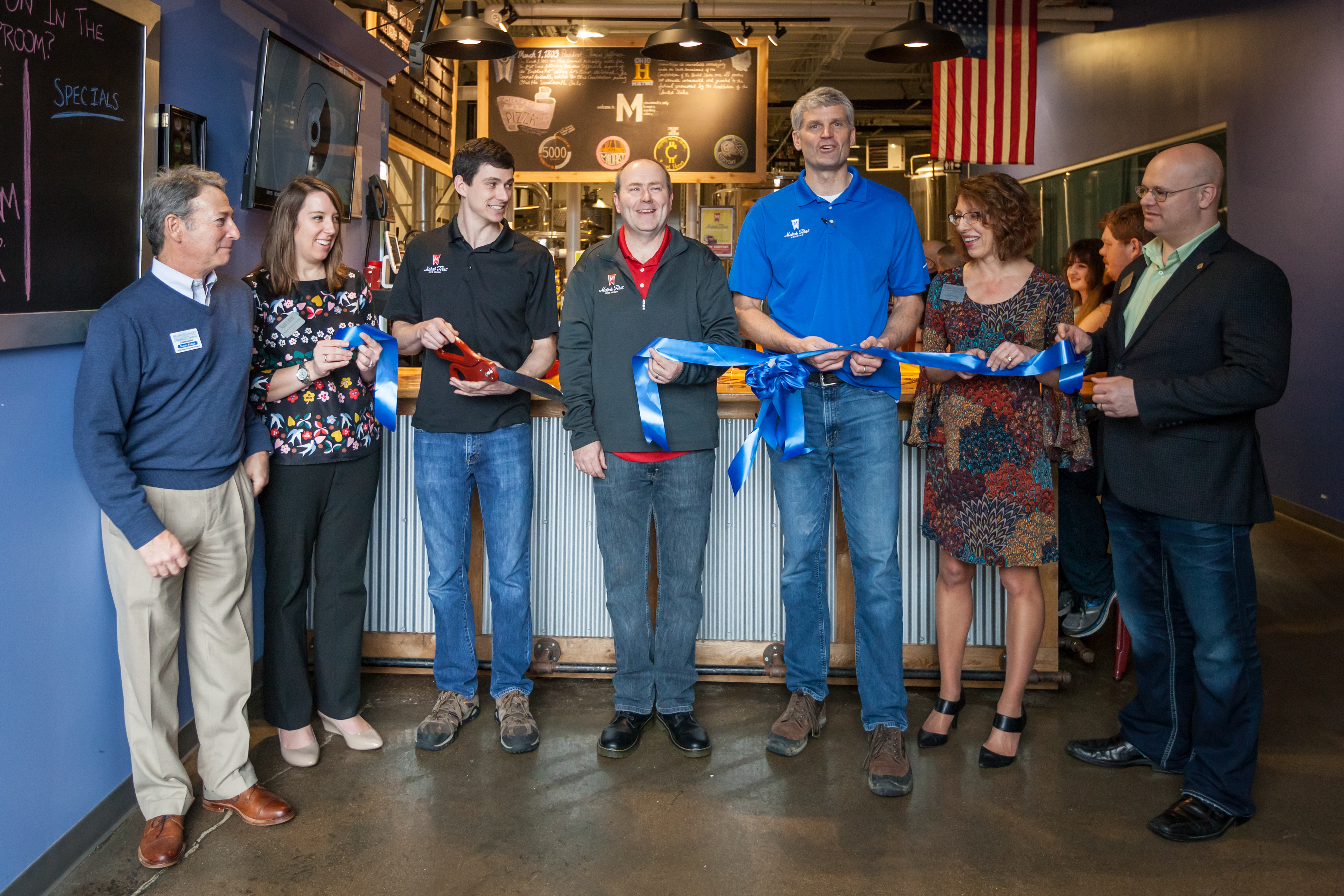 Seven people smiling while one cuts a blue ribbon with large red scissors