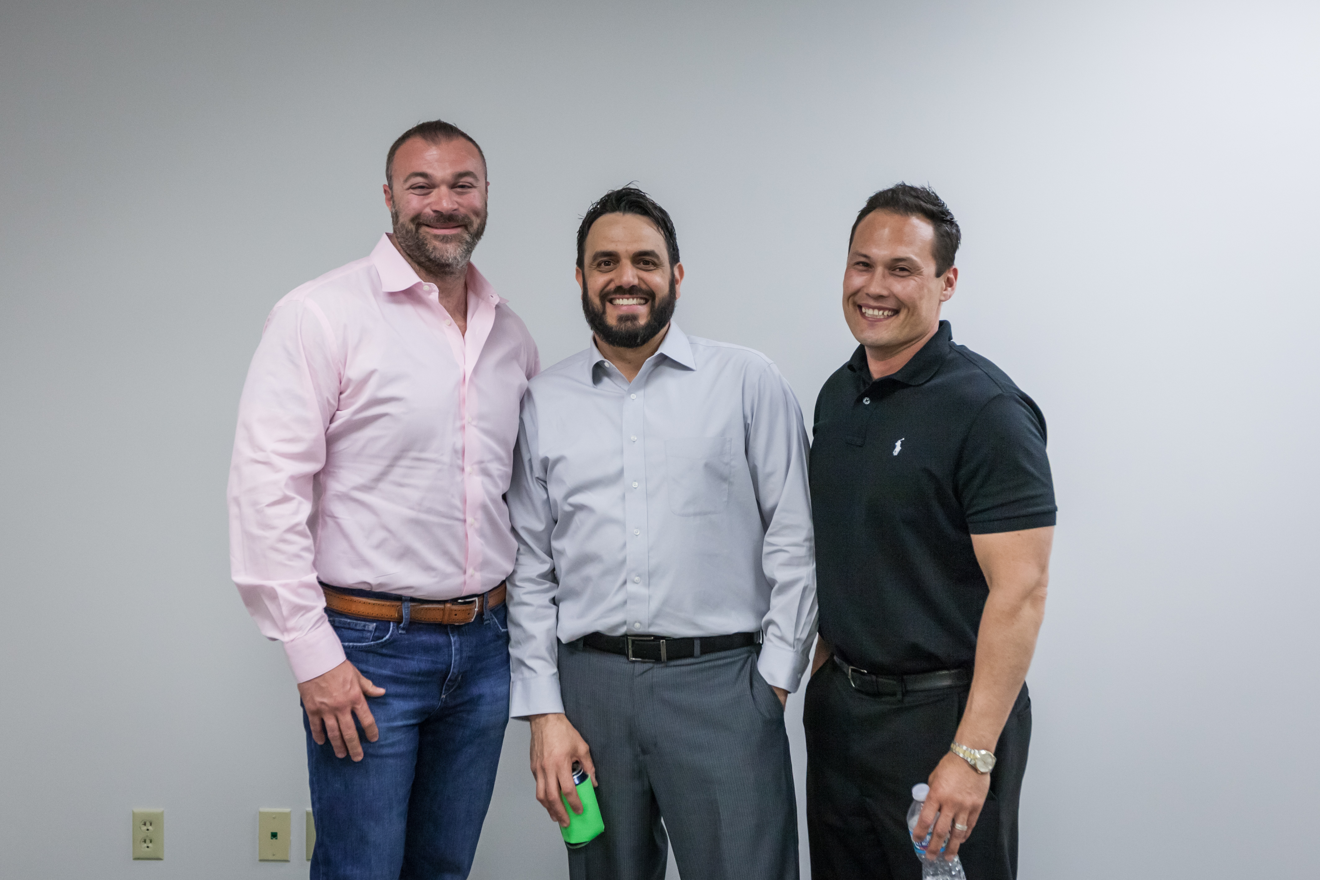 Three men standing side by side smiling for picture
