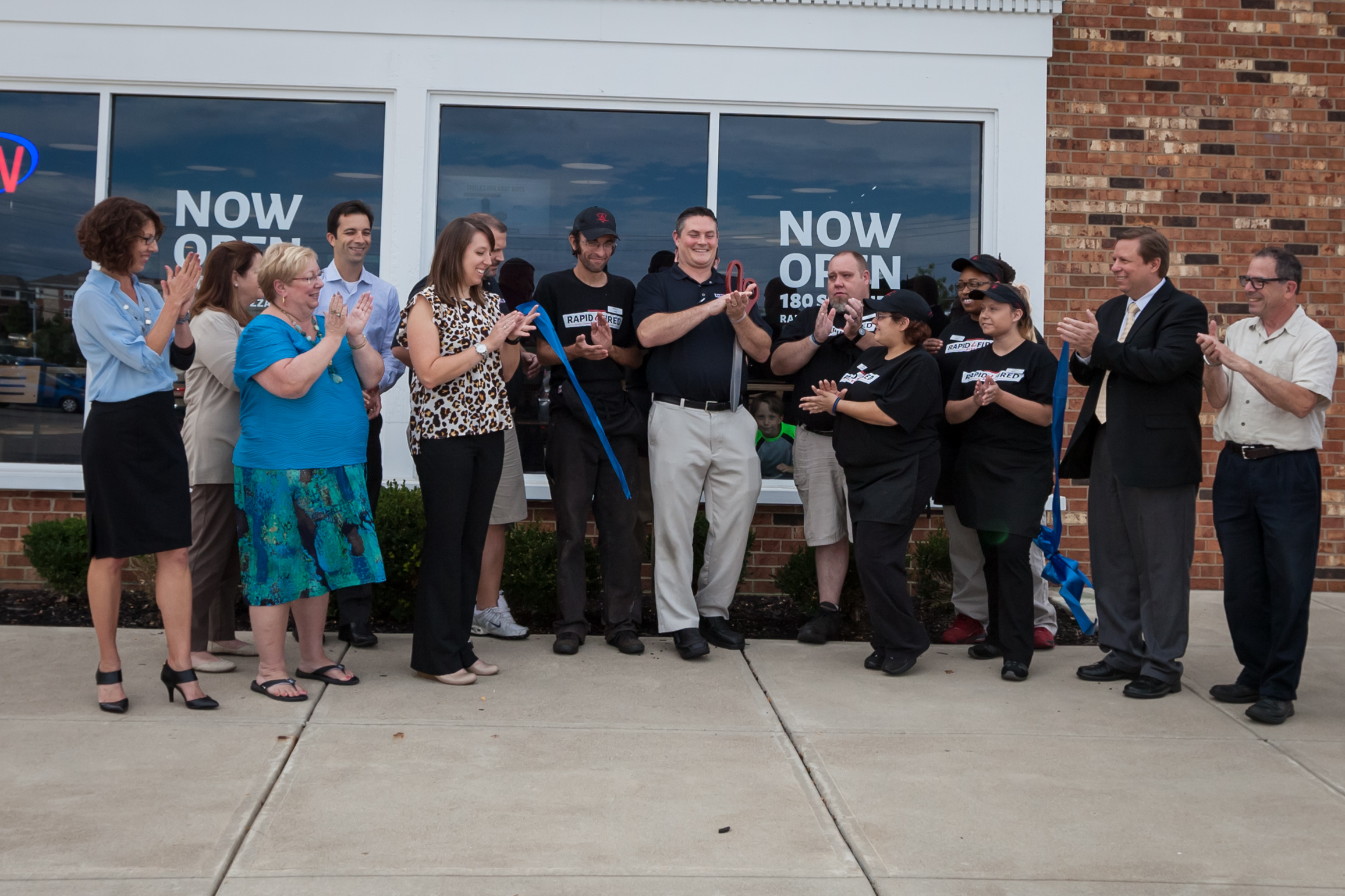 Thirteen people in front of a business Grand Opening clapping