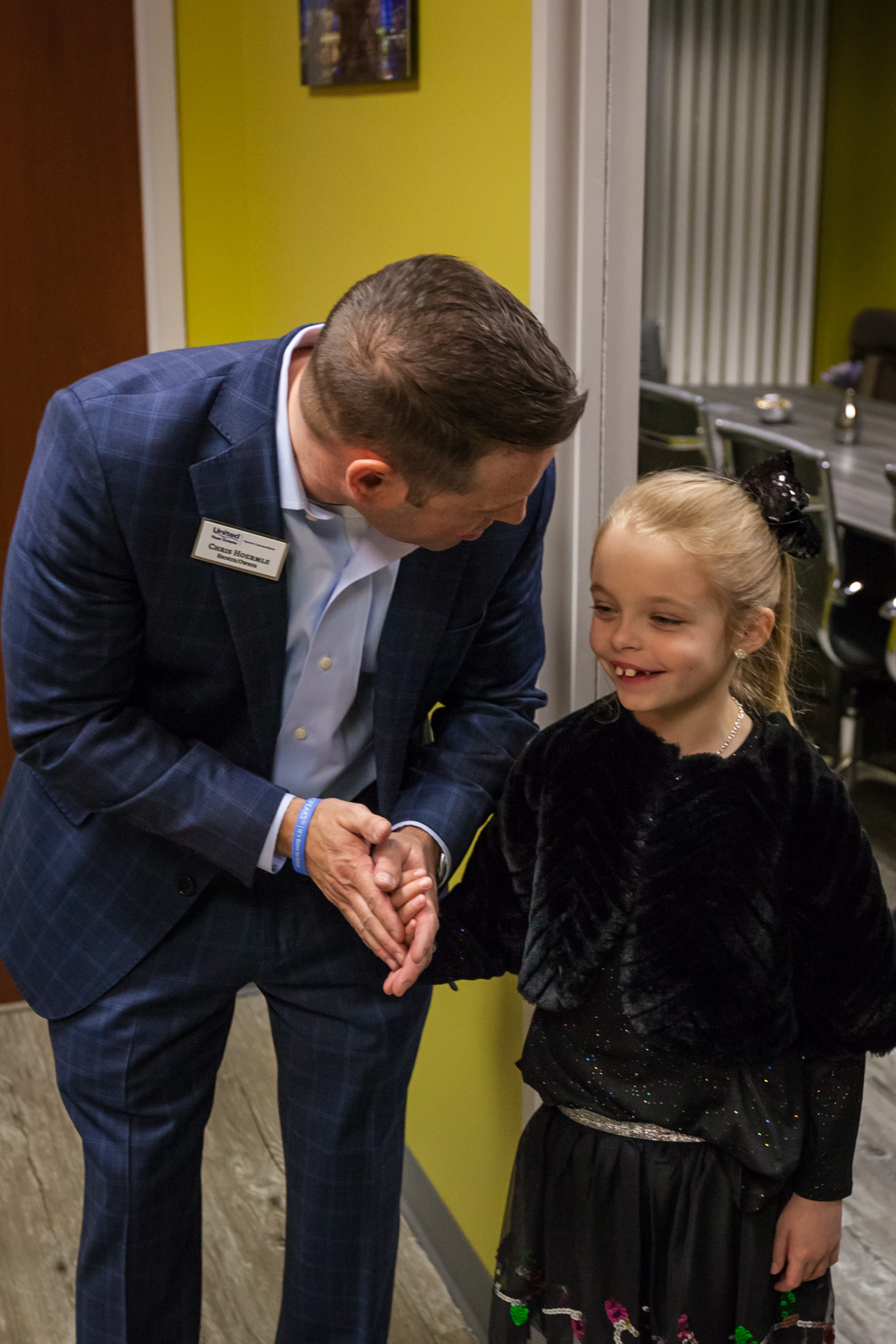 A man in a suit talking to a young girl