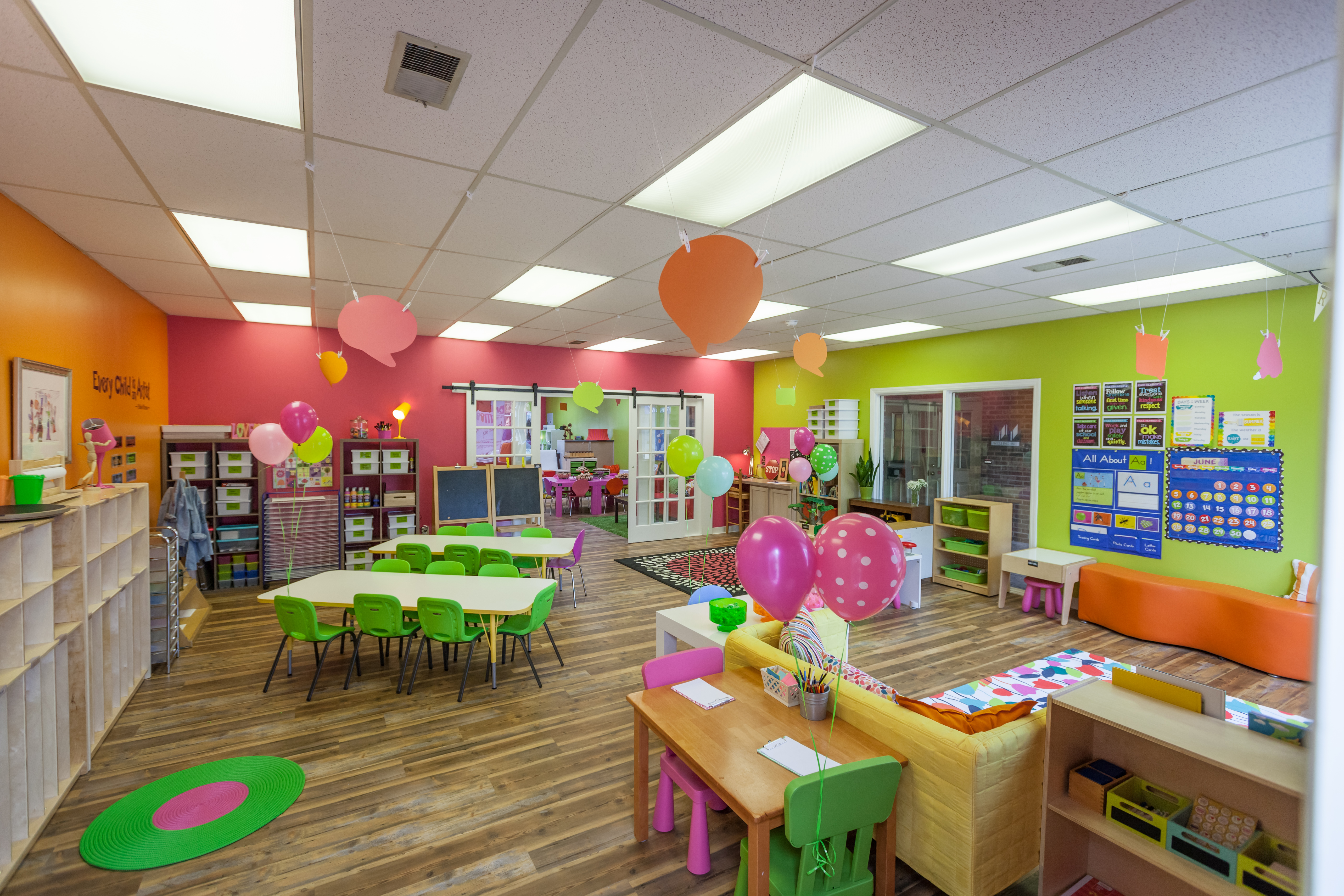 A room with lots of balloons and tables set up